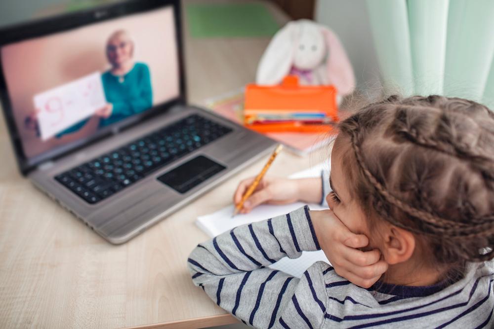 Girl watching online teacher tutoring