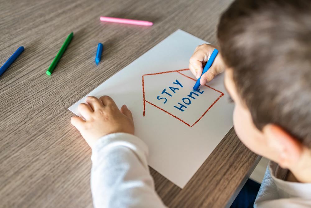 Little boy drawing at home coronavirus