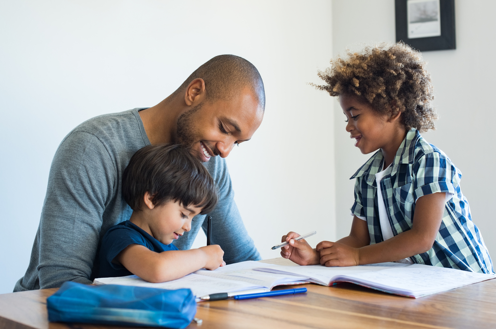 Black father teaching his son white rose maths from home