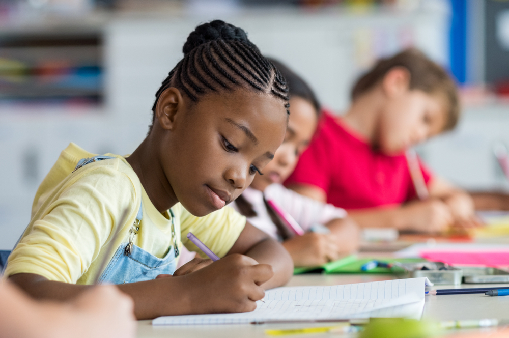 Girl writing in class with other children