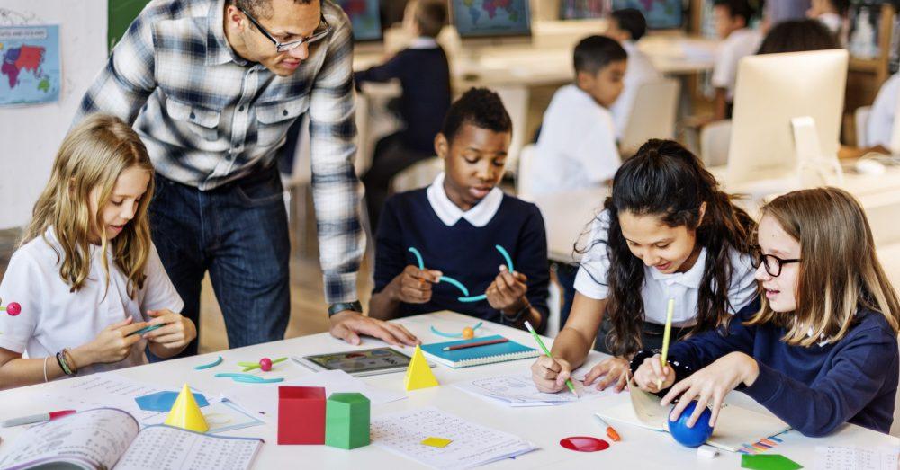 children and teacher in a classroom doing white rose maths activities