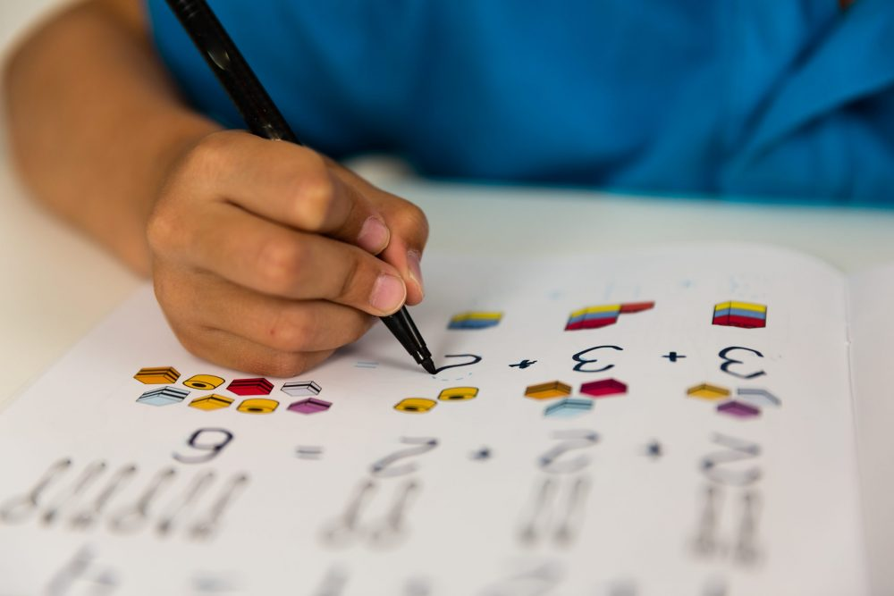 child completing a white rose maths worksheet