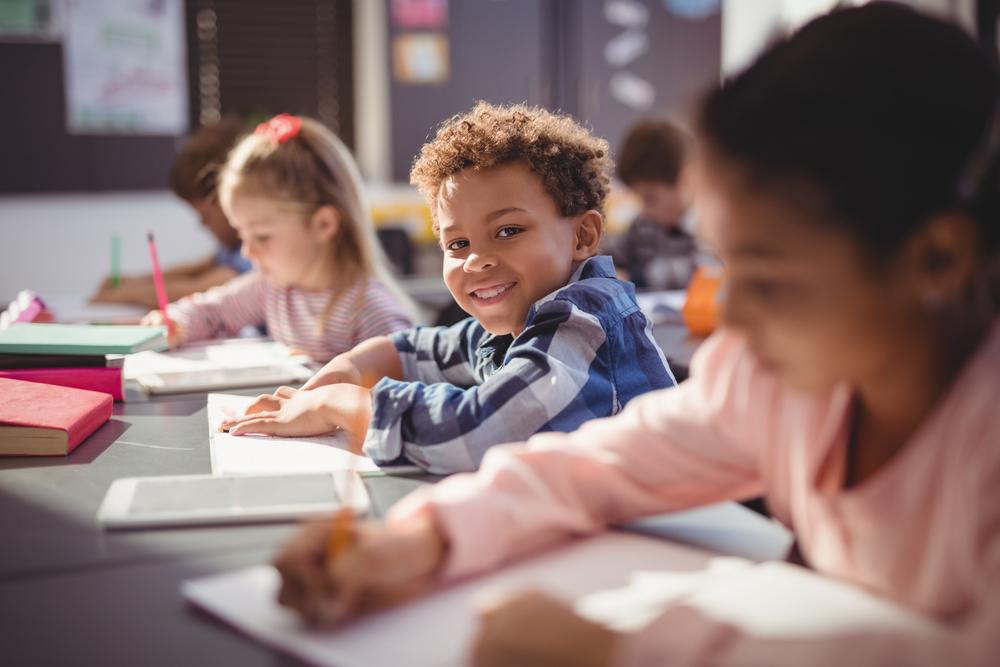 Three children writing in notebooks in school class